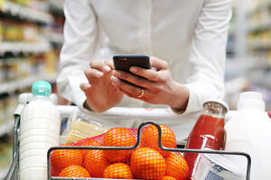 Woman looking at phone in Supermarket